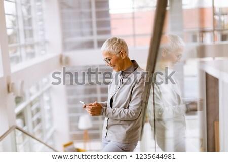 senior businesswoman using mobile phone in modern ofice stock photo © boggy