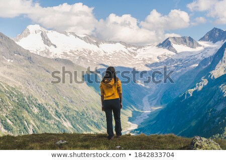 woman with backpack and camera over alps mountains stock photo © dolgachov