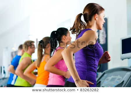 Young woman exercise on the treadmill at the gym Stock photo © boggy