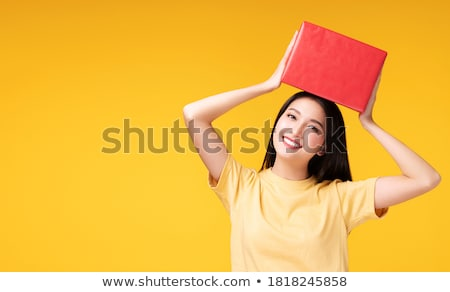 emotional happy young friends women standing isolated over red background holding gift box surprise stock photo © deandrobot