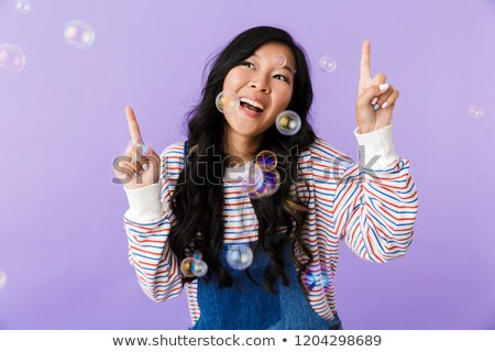 Asian beautiful attractive woman posing isolated indoors pointing over soap bubbles. Stock photo © deandrobot