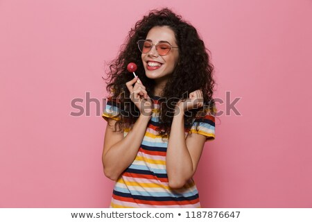 Happy cute young woman posing isolated over pink background eat candy lollipop. Stock photo © deandrobot