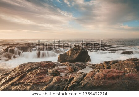 Sunlight hitting the rocks with ocean waterfall cascades Foto stock © lovleah