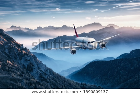 white airplane is flying over mountains and low clouds stock photo © denbelitsky