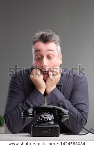 anxious man looking at a phone in trepidation stock photo © giulio_fornasar
