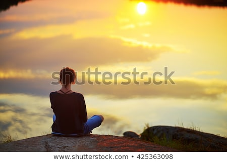 Relaxed woman watching a serene sunset by the lake Stock photo © lovleah