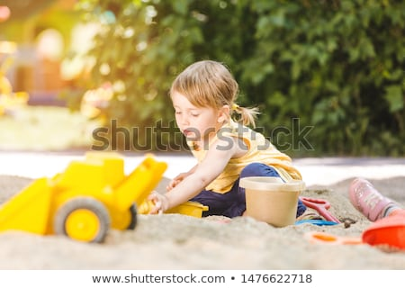 Little girl having lots of fun with her toys playing in the sandbox Stock photo © Kzenon