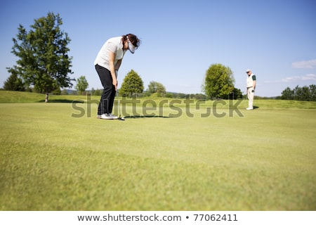 Old golfer shooting on green. Stock photo © lichtmeister
