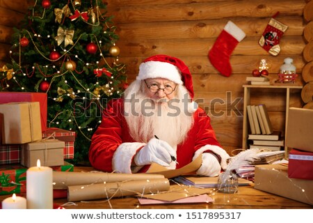 kind santa in costume and white gloves writing christmas letters to kids stock photo © pressmaster