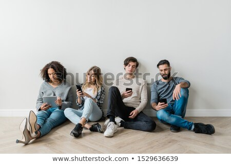Intercultural milennials with smartphones sitting by white wall while texting Stock photo © pressmaster