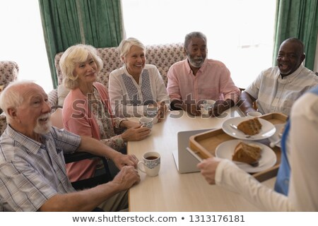 front view of group of happy senior people having black coffee with cake in living room at home stock photo © wavebreak_media