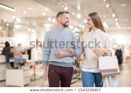 Cheerful young couple carrying paperbags while leaving clothing department Stock photo © pressmaster