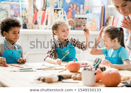 One of naughty schoolgirls in blue aprons hit the other with pinecone at lesson Stock photo © pressmaster