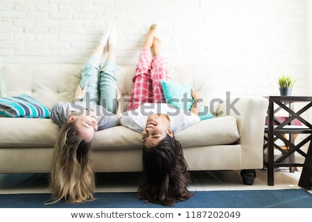 Image of young woman smiling while lying upside down on sofa at  Stock photo © deandrobot