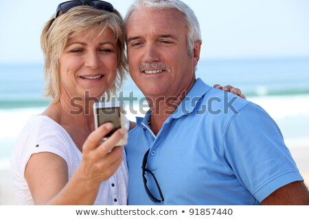 Stock photo: Mature couple taking a picture of themselves by the sea