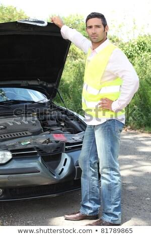 Man wearing high visibility jacket stood inspecting car engine Stock photo © photography33