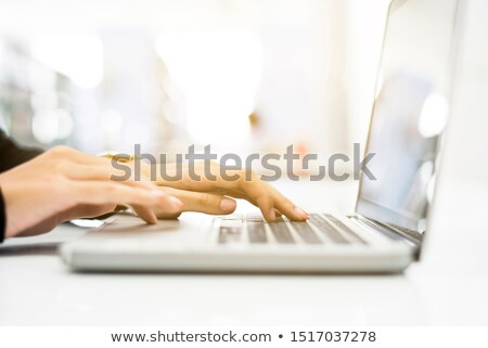 Stock photo: Closeup image of female hands typing on laptop keypad