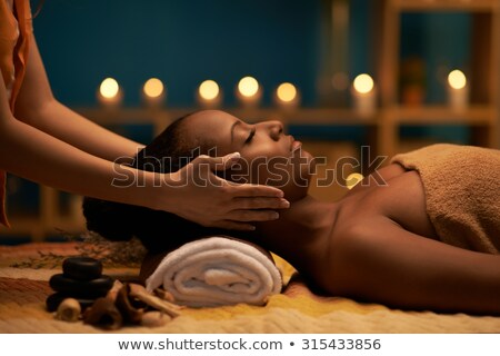 Masseur doing massage to african woman Stock photo © HASLOO