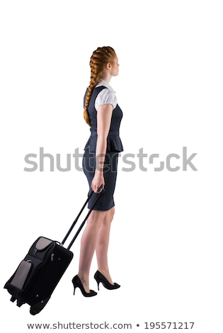 Stock photo: Redhead businesswoman pulling her suitcase