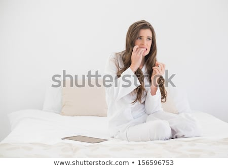 Pretty brunette biting nails with anxiety Stock photo © wavebreak_media
