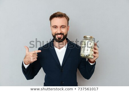 Cool young men with a money box on a grey background stock photo © Patramansky