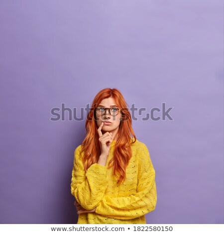 thoughtful pretty redhead young woman standing and thinking stock photo © deandrobot