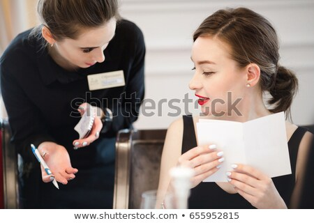 Two women talking to waitress and making order in cafe  Stock photo © deandrobot