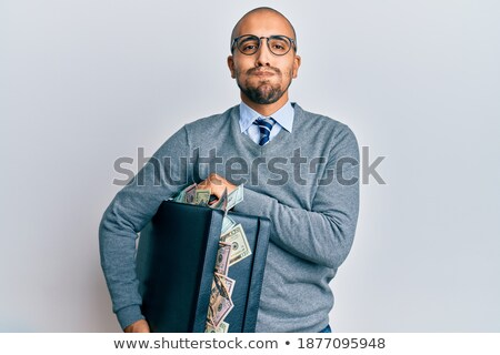 Hispanic businessman with briefcase full of money Stock photo © RAStudio