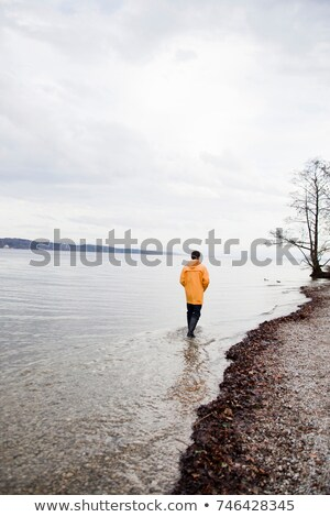 man in raincoat wading along shore Stock photo © IS2
