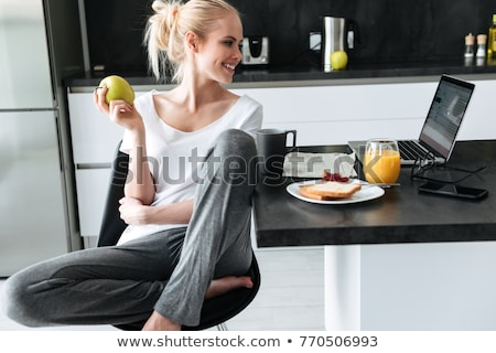 Young lady eating apple and using laptop in kitchen Stock photo © deandrobot