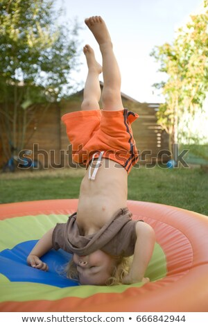Young boy doing headstand on trampoline Stock photo © IS2