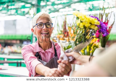 Senior woman sales flowers on local flower market Stock photo © boggy