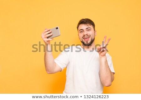 Man permanente geïsoleerd smartphone tonen Stockfoto © deandrobot