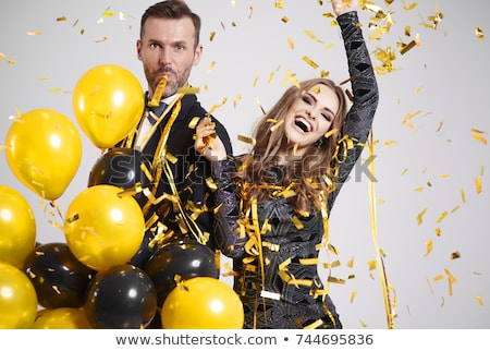 Stok fotoğraf: Happy Couple With Party Blowers Having Fun