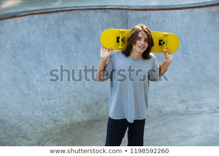 Smiling young teenge boy spending time at the skate park Stock photo © deandrobot
