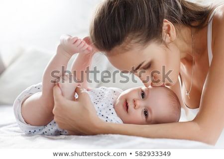 Portrait of beautiful mom playing with her 8 months old baby in bedroom, top view Stock photo © Lopolo