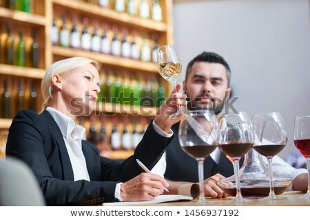 Serious professional sommeliers examining color of white wine in bokal Stock photo © pressmaster