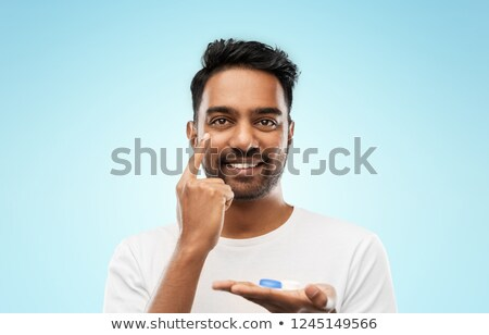 young indian man applying contact lenses Stock photo © dolgachov