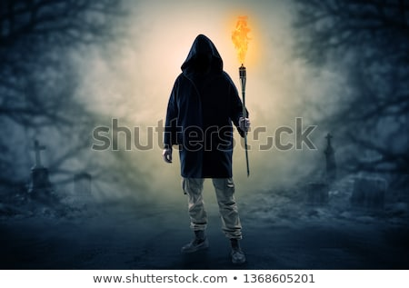 Man coming out from a thicket with burning flambeau Stock photo © ra2studio