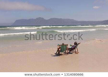 rear view of senior couple relaxing on sun lounger and drinking cocktail on beach in the sunshine stock photo © wavebreak_media
