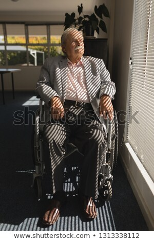 Front view of disable senior man sitting on wheelchair and looking outside through window at home Stock photo © wavebreak_media