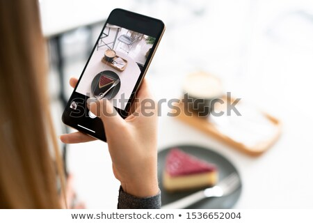 cappuccino and tiramisu cake on touchscreen of smartphone held by young woman stock photo © pressmaster