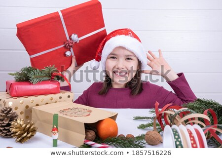 Woman and child on Christmas with wrapped gifts and Santa Claus caps Stock photo © Kzenon