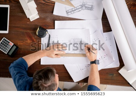 Overview of contemporary engineer sitting by table and correcting sketches Stock photo © pressmaster