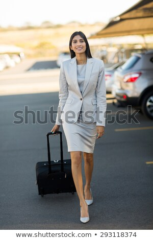 Young elegant businesswoman of Asian ethnicity pulling suitcase in airport Stock photo © pressmaster