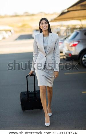 Fiatal elegáns üzletasszony ázsiai származású húz bőrönd Stock fotó © pressmaster