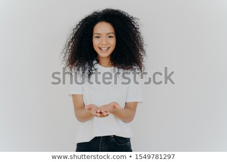 Glad dark skinned woman has cupped hands, asks to give something, smiles plesantly, has bushy frizzy Stock photo © vkstudio