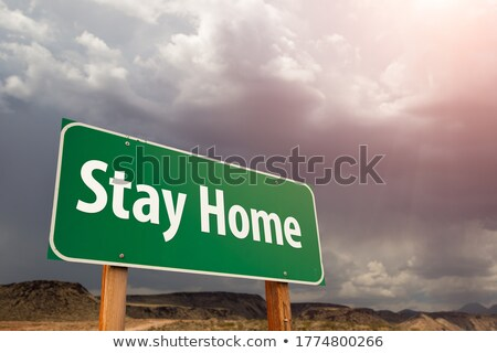 Stay At Home Green Road Sign Against An Ominous Cloudy Sky Stock photo © feverpitch