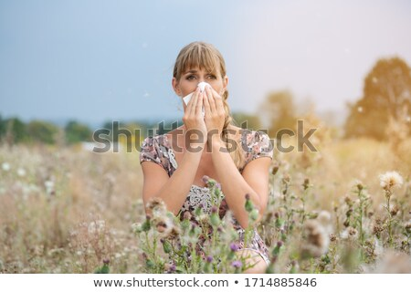 Woman in meadow snorts in handkerchief Stock photo © Kzenon