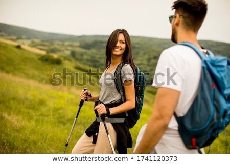 Smiling couple walking with backpacks over green hills Stock photo © boggy